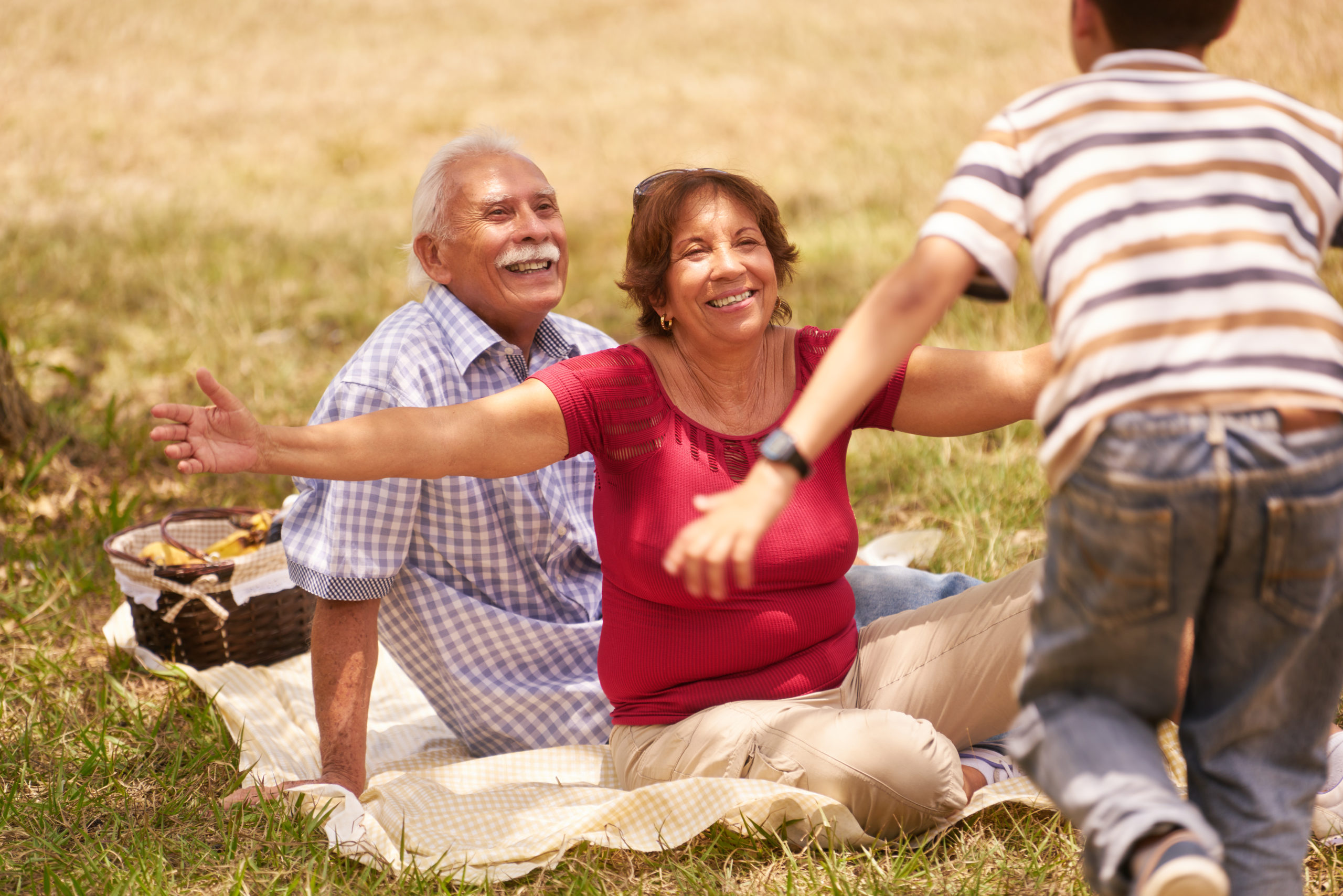 Old people, senior couple, elderly man and woman. Outdoor family having fun with happy grandpa and grandma hugging boy at picnic in park.