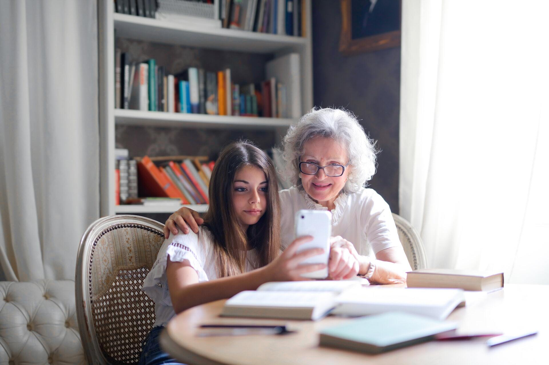 woman-showing-her-cellphone-to-her-grandmother-3768148