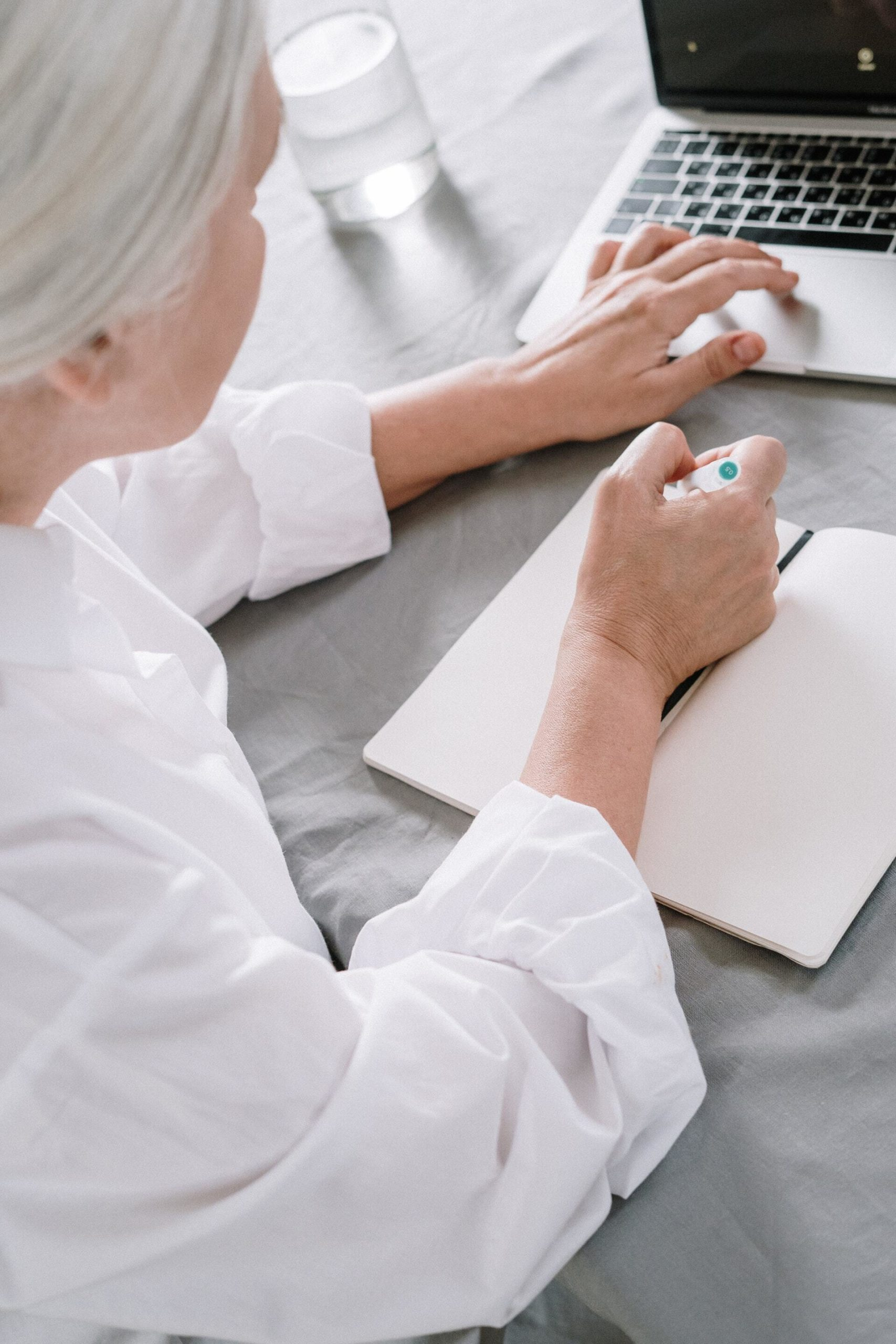 an-elderly-woman-taking-notes-while-using-a-laptop-4057764